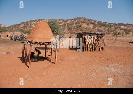 Himba tribe village, Kaokoveld, Namibia, Africa. The shed on the right is used for storage of grain or livestock - Stock Photo