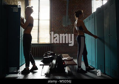 Side view of two tough women in shabby changing room in sports club , copy space - Stock Photo