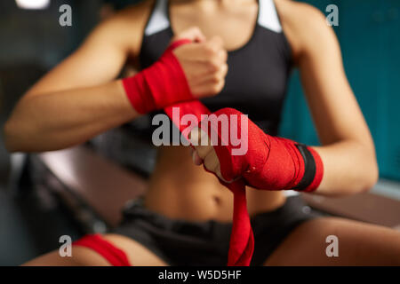Close up of tough young woman putting on red hand wraps preparing for boxing practice in sports club, copy space