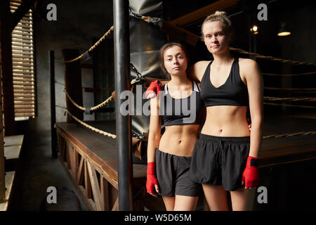 Portrait of two female boxers posing together standing against boxing ring and looking at camera, copy space - Stock Photo