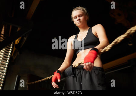 Dramatic low angle portrait of tough female boxer looking down at camera while standing in boxing ring, copy space - Stock Photo