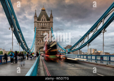 Tower Bridge in London, UK in evening with moving red double-decker bus leaving light traces, United Kingdom. - Stock Photo