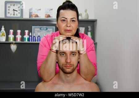 professional therapeutic neck and head massage. man the athlete in a massage room. pain recovery procedure. Female physiotherapist doing manipulative - Stock Photo