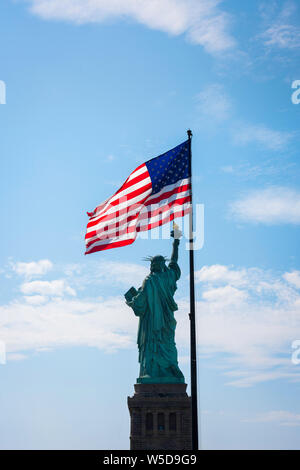 USA freedom, view of the rear of the Statue of Liberty and a back-lit stars and stripes flag, Liberty Island, New York City, USA. - Stock Photo