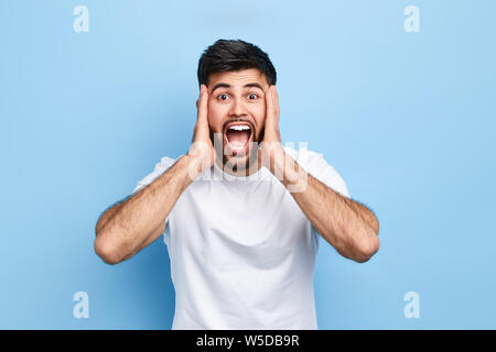 disappointed confused man touches his cheeks with palms, expresses puzzlement, surprise. close up portrait. isolated blue background, studio shot. neg - Stock Photo