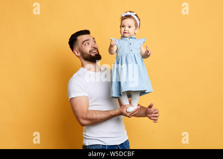 Happy unforgettable moments, excited handsome man rejoicing at his daughter's achievment. daddy teaches his daughter to stand, doing exercises. happy - Stock Photo
