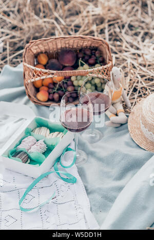 Two glasses of red wine, fruits and sweets on the sunset picnic. Top view. - Stock Photo