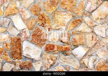 Masonry wall of stones with irregular pattern texture background - Stock Photo