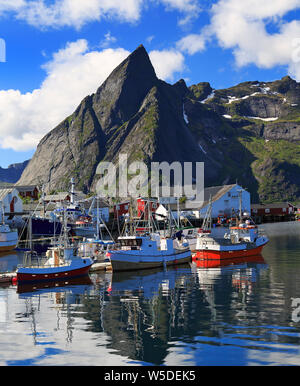 Traditional Norwegian fishing boats in Lofoten Island, Reine area with nice reflections in the ocean fjord - Stock Photo