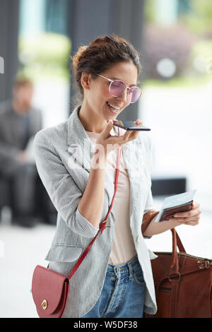 Excited young woman in pink sunglasses standing in airport and holding passport with boarding pass while recording audio message - Stock Photo