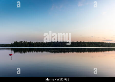 Reflections on the calm waters of the Saimaa lake in Finland at Sunset  - 4 - Stock Photo