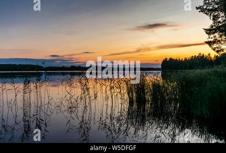 Reflections on the calm waters of the Saimaa lake in Finland at Sunset  - 1 - Stock Photo
