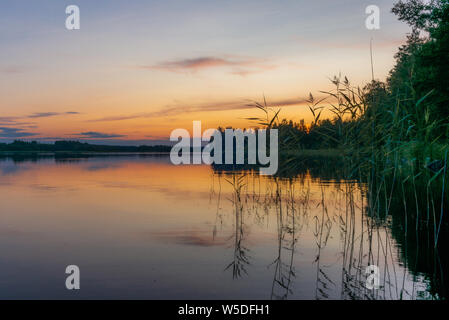 Reflections on the calm waters of the Saimaa lake in Finland at Sunset  - 5 - Stock Photo
