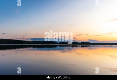 Reflections on the calm waters of the Saimaa lake in Finland at Sunset  - 3 - Stock Photo
