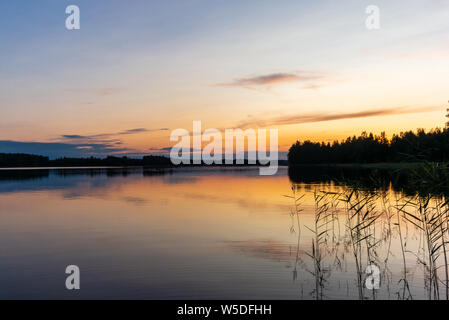 Reflections on the calm waters of the Saimaa lake in Finland at Sunset  - 2 - Stock Photo