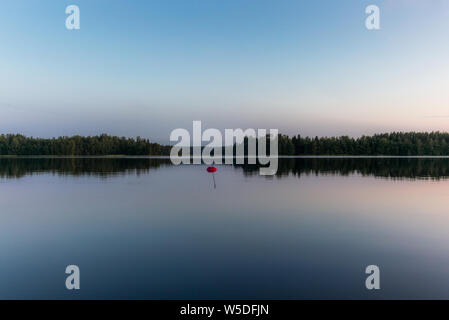 Reflections on the calm waters of the Saimaa lake in Finland at Sunset  - 6 - Stock Photo