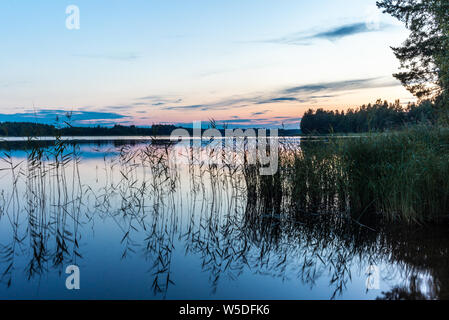 Reflections on the calm waters of the Saimaa lake in Finland at Sunset  - 11 - Stock Photo
