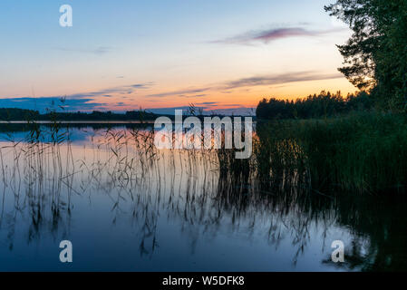 Reflections on the calm waters of the Saimaa lake in Finland at Sunset  - 8 - Stock Photo