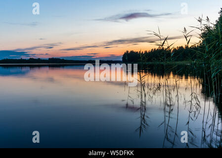 Reflections on the calm waters of the Saimaa lake in Finland at Sunset  - 9 - Stock Photo