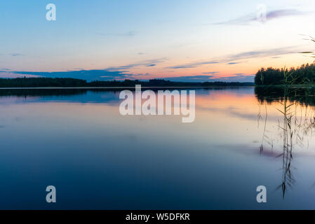 Reflections on the calm waters of the Saimaa lake in Finland at Sunset  - 10 - Stock Photo