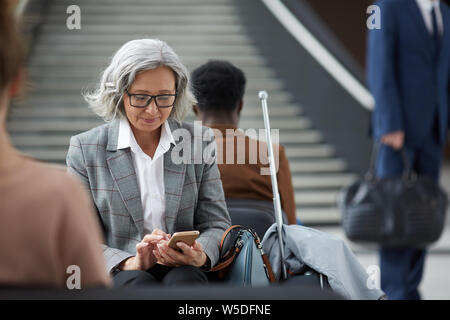 Content elderly Asian woman with gray hair wearing eyeglasses sitting in waiting area of airport and using mobile app on gadget - Stock Photo
