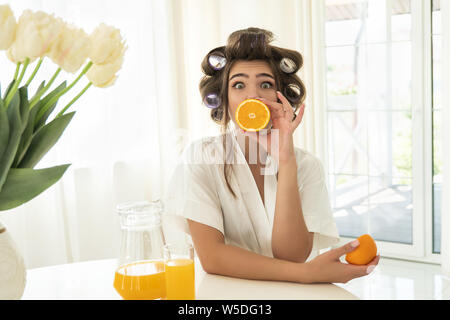 beautiful young surprised brunette woman in hair curlers holding one orange near her mouth and another in her hand in bright kitchen - Stock Photo