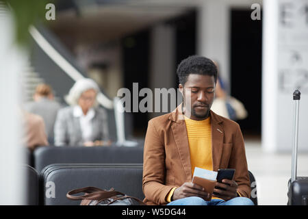Serious pensive young black man with beard sitting in airport and communicating via online app on phone - Stock Photo