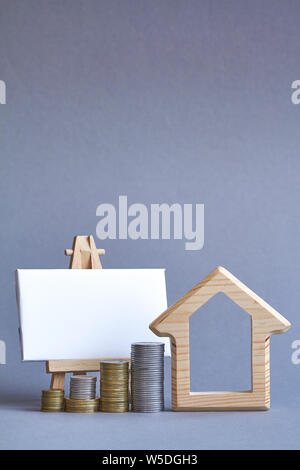 A wooden figure of house with several columns of coins nearby and white board on miniature easel on gray background, the concept of buying or renting - Stock Photo