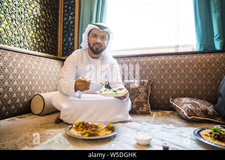 Arabic man with traditional clothes eating chicken mandy, in Dubai - Stock Photo