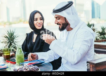Happy couple spending time in Dubai. man and woman wearing traditional clothes having a conversation in a cafe - Stock Photo