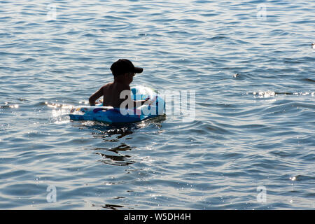 Boy swims in the lake. Around a lot of spray and foam. One child swims on the lake - Stock Photo