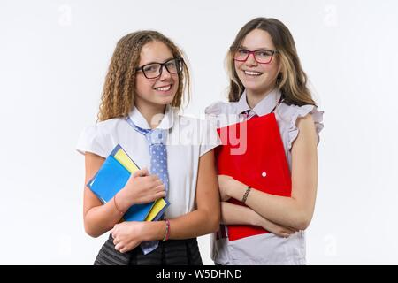 Two smiling high school girls in uniform wearing glasses with notebooks posing on white background - Stock Photo