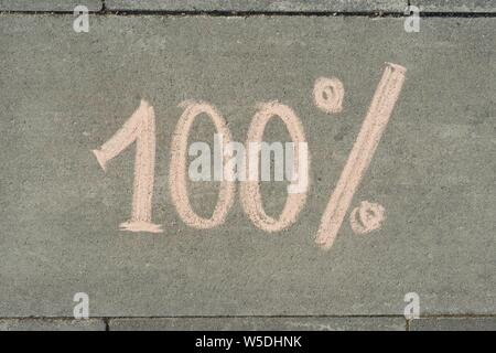 Abstract text 100 percent written on grey sidewalk - Stock Photo