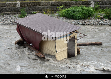 A small house destroyed the mudflow in the mountains. A small house was washed away by a flooded mountain river. The devastating effects of a flood or - Stock Photo