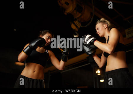 Dramatic low angle portrait of two women fighting in boxing ring, copy space - Stock Photo
