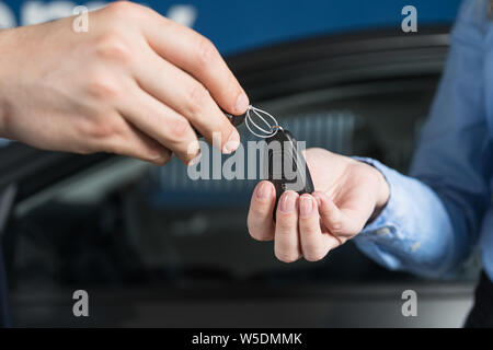 Salesman handing over car keys to new female owner. New or used vehicle buying concept. - Stock Photo