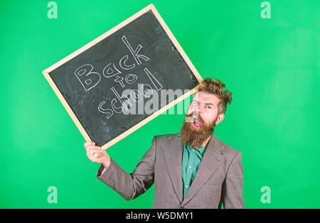 Teacher bearded man holds blackboard with inscription back to school green background. Keep working. Teacher with tousled hair stressful about school year beginning. Teaching stressful occupation. - Stock Photo