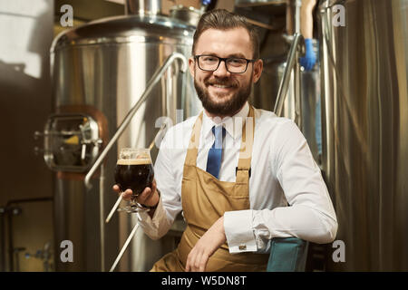 Positive, cheerful brewer sitting on steps of metal platform, holding glass with dark beer. Handsome worker smiling and posing on background of steel storage tank. - Stock Photo