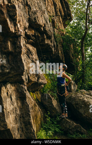 Young beautiful girl wearing in climbing equipment standing in front of a stone rock and preparing to climb against brown cracked rock and trees - Stock Photo