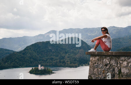 Young smiling woman tourist sitting on a Bled Castle wall with the lake Bled and the Bled island on the background. Surrounded by mountains and forest - Stock Photo