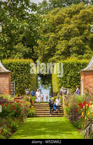 People enjoying the day out at the  National trust property of Hidcote Manor gardens with its herbaceous flower borders in the English Cotswolds - Stock Photo