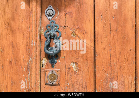 Metal doorknocker on an aged wooden door with cracked paint (close-up, landscape format) - Stock Photo