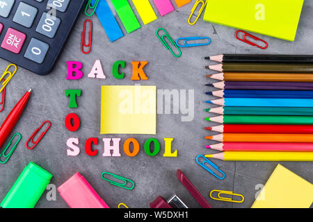 The layout of school supplies on a dark gray background. The view from the top. Flat lay - Stock Photo