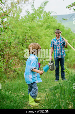 small boy child help father in farming. happy earth day. Family tree nursering. watering can, pot and hoe. Garden equipment. Eco farm. father and son in cowboy hat and rubber boots on ranch. - Stock Photo