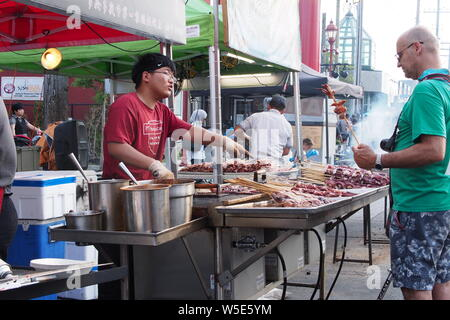 Man buying and another man selling squid on a stick at the Ottawa Asian Fest Night Market, 2019. Ottawa, Ontario, Canada. - Stock Photo