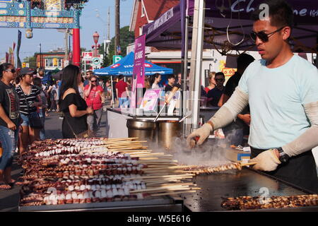 Man grilling and serving tentacles on a stick at the Ottawa Asian Fest Night Market, 2019. Ottawa, Ontario, Canada. - Stock Photo