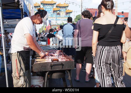 Squid tentacles on a stick being prepared and sold at the Ottawa Asian Fest Night Market, 2019. Ottawa, Ontario, Canada. - Stock Photo