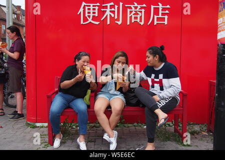 Three people enjoying the delights on offer at the Ottawa Asian Fest Night Market, 2019. Ottawa, Ontario, Canada. - Stock Photo