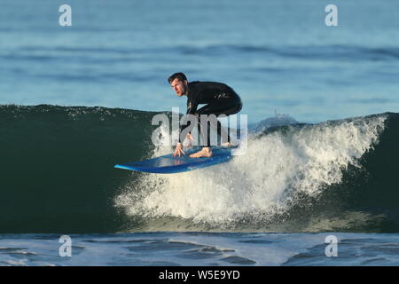 Young man wearing a black wetsuit riding a blue surfboard in Huntington Beach, California on October 19, 2018 - Stock Photo