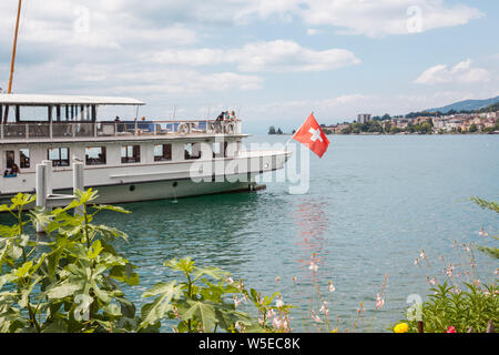 The Belle Epoque retro paddle boat with Swiss flag at the stern moored in Montreux, Lake Geneva (lac Leman), Vaud, Switzerland on sunny summer day - Stock Photo